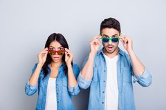 Oh my God! Shocked partners  with wide opened mouths and eyes pe. Ering out summer glasses  over grey background Stock Photography