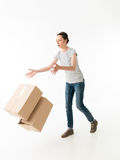 Oh no!. Clumsy young woman dropping moving boxes and tripping. on white background Royalty Free Stock Photo