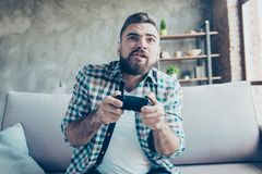 Oh, no! I can`t lose! Excited cheerful nervous handsome joyful b. Earded guy wearing checkered shirt and white tshirt is playing videogames at home, sitting on royalty free stock image