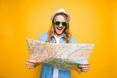 Oh no! Portrair of young shocked man looking in open road map on. Yellow background. A tourist on summer vacation. Adventures seeker royalty free stock photo