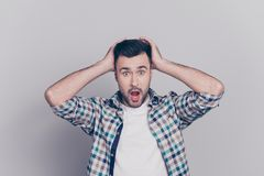 Oh no! Portrait of surprised, shocked man with stubble and wide. Opened mouth and eyes in checkered shirt touching head with two hands isolated on grey royalty free stock photography