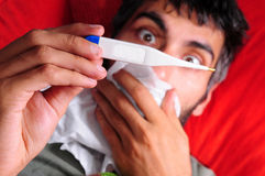 Oh No! Sick Man Checking for a Fever Royalty Free Stock Photo