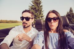 Oh no! Wtf! Close up of gorgeous brunette lady driver and her br. Unet guy panicking, both well dressed, in black trendy eyewear, park with green trees around Royalty Free Stock Photos