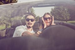 Oh no! Wtf! Front view, windscreen, guy grabs steering wheel while lady driver is panicking, both well dressed, in black trendy e. Yewear, woods around, sunny royalty free stock image