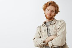 Oh not impressive. Portrait of cool snobbish redhead guy with wavy hair and beard tilting backwards with hands crossed. On chest and doubtful unimpressed stock photo