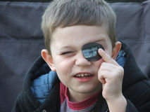 Oh, NOW I can see!. Young boy holding a spectacle lens to one eye royalty free stock photography