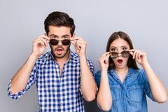 Oh really?! Wow! Two young shocked lovers are amazed with wide open eyes, mouthes, touching sun glasses, standing in a casual wear. On light background royalty free stock photography
