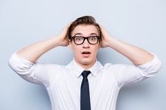 Oh wow! Really?! Young handsome student is shocked, holding his. Head, in a formal outfit and black stylish glasses, standing on pure background stock photo