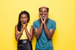 Ohh Dio Ritratto di giovani grida afroamericani sorpresi delle coppie isolati sopra fondo giallo fotografia stock