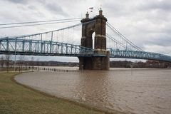 Ohio River above flood stage and John Roebling Suspension Bridge royalty free stock photo