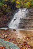 Ohio's Buttermilk Falls. Buttermilk Falls, a waterfall in Cuyahoga Valley National Park, spills whitewater over a shale cliff with many tiny ledges in the autumn Stock Images