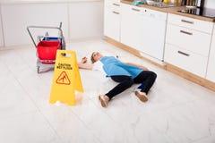 In Ohnmacht gefallene Hausgehilfin, die auf Boden in der Küche liegt stockfoto