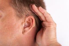 Ohr eines tragenden Hörgerätes und des Höhlens des Mannes seiner Hand hinter seinem Stockfotografie
