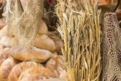 Ohren des Roggenkornes und Haufen von frisch gebackenen traditionellen Broten Lizenzfreies Stockfoto