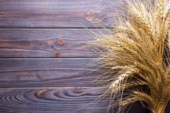 Ohren des Weizens auf altem Holztisch Stockfotografie