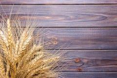 Ohren des Weizens auf altem Holztisch Lizenzfreie Stockfotos