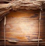 Ohren des Weizens auf altem Holztisch Lizenzfreie Stockfotografie