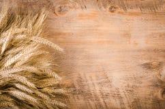 Ohren des Weizens auf hölzernem Hintergrund Feld Lizenzfreies Stockfoto