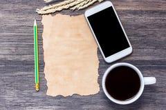 Ohren des Weizens, des intelligenten Telefons und des alten Papiers mit Tasse Kaffee stockfotos