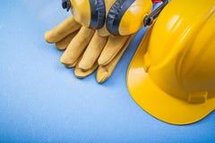 Ohrenschützerschutzhandschuhe, die Sturzhelm auf blauem Hintergrund constr errichten Stockfotos