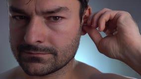 Ohrenstöpsel in ihre Ohren, die auf Geräusche setzen im lauten Platz gereinigt erhalten stock video