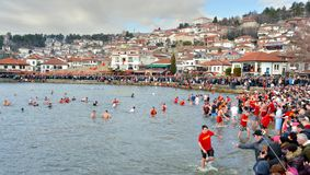 OHRID, MACEDONIA - JANUARY 19, 2017: Men swim in the cold water to retrieve the cross at the Epiphany in Ohrid, Macedonia. OHRID, MACEDONIA - JANUARY 19, 2017 Stock Photos