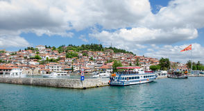 Ohrid in Macedonia. View of Ohrid old city and Ohrid lake( the most popular and most visited landmark in Macedonia) with waving Macedonian flag and several boats Royalty Free Stock Image