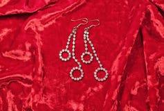 Ohrringe der Frau auf rotem Samthintergrund Stockbilder