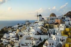 Oia白色大厦townscape和风车美好的晚上光场面沿海岛山,浩大的海洋,软的云彩 免版税库存照片