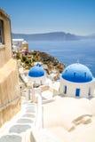 oia看法santorini的和一部分的破火山口,蓝色教会 库存照片