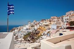 Oia πανόραμα και ελληνική σημαία Στοκ Εικόνα