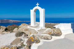 Oia. Aerial view of the village from above. The church arch with cross on top of a mountain over  island Santorini and  village Oia. Greece Royalty Free Stock Photo