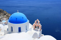 Oia Blue Dome and Pink Bell Tower. Oia is a community on the islands of Thira (Santorini) and Therasia, in the Cyclades, Greece. The population was 1,230 Stock Photo