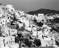 Oia Cityscape On Santorini. A view of the town of Oia on the Greek island of Santorini. The city snakes along the top of the hill which is the rim of an old Stock Photos