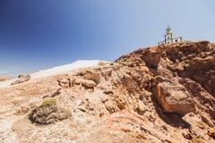 Oia en la isla de Santorini Grecia caldera Faro en un acantilado Rocas imagenes de archivo