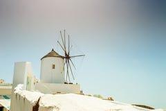 风车在Oia镇 在圣托里尼海岛, Gr上的白色建筑学 免版税库存照片