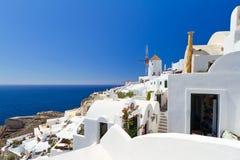 Oia by på Santorini med vitwindmillen Fotografering för Bildbyråer
