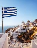 oia santorini 在峭壁边的风车和希腊旗子 免版税库存图片