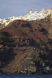 Oia, Santorini. A view from the water up at the village of Oia, Santorini. The village balances on the edge on top of steep cliffs Stock Images