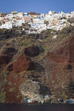 Oia, Santorini. A view from the water up at the village of Oia, Santorini. The village balances on the edge on top of steep cliffs Stock Image