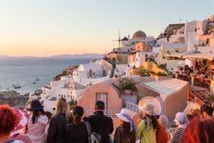 Indian tourists taking photos of colorful Oia village on Santorini island, Greece. stock image