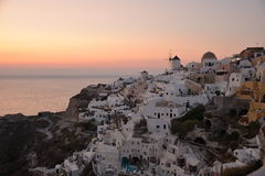 Oia, Santorini, Greece. Sunset at Oia, a village in the north of the Greek island of Santorini with whitewashed houses, small hotels and churches with a windmill Stock Image