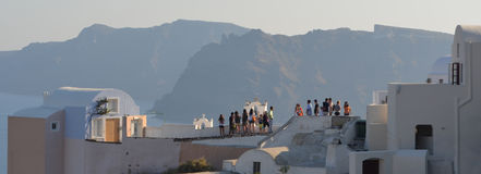 Oia Santorini Tourists on roof tops Thirassia Island Royalty Free Stock Photography