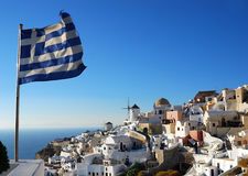 Oia scenery with Greece flag, Santorini Stock Photo