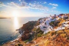 Oia stad på den Santorini ön, Grekland på solnedgången Berömd väderkvarn Royaltyfri Bild