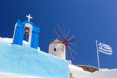 Oia-Stadt auf Santorini-Insel, Griechenland Berühmte Windmühlen, Kirche, Flagge Lizenzfreies Stockfoto