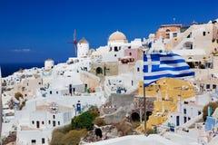 Oia-Stadt auf Santorini-Insel, Griechenland Wellenartig bewegende griechische Flagge Stockfoto
