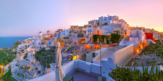 Oia at sunset, Santorini, Greece. Panoramic famous view, Old Town of Oia or Ia on the island Santorini, white houses and windmills at dawn, Greece Royalty Free Stock Images