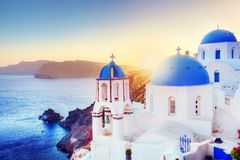 Oia town on Santorini Greece at sunset. Aegean sea. Oia town on Santorini Greece at sunset. Traditional and famous white houses and churches with blue domes over Stock Photo