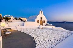 Oia town, Santorini island, Greece at sunset. Traditional and fa. Mous white churches  over the Caldera, Aegean sea Stock Photo